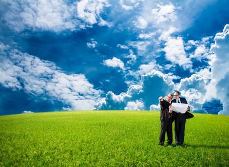 Zwei Männer stehen mit einem Lageplan auf einer grünen Wiese