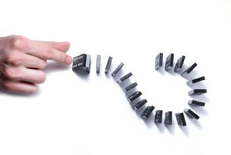 Dominosteine in Fragezeichenform angeordnet, Finger einer Hand schnippt gegen den ersten Stein