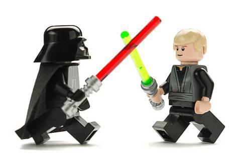 Zwei Lego-Spielfiguren der Star Wars-Serie von Lego kämpfen mit Laserschwertern
