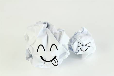 Zusammen geknüllte Papierknäuel mit lachendem Gesicht