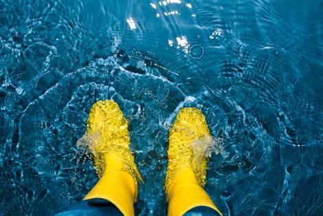 Man schaut auf gelbe Gummistiefel herunter, die im seichten, blauen Wasser stehen
