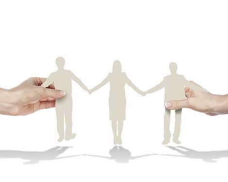 Zwei Hände einer Person halten vom äußeren Bildrand eine Dreierreihe ausgeschnittener Papierfiguren.