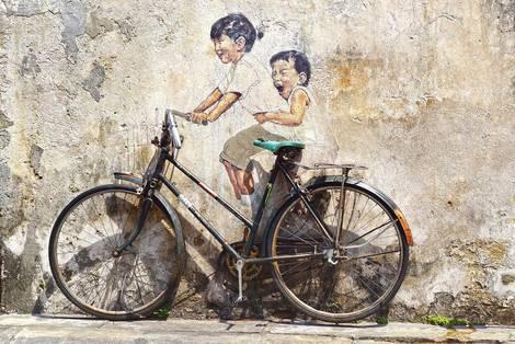 Fahrrad steht vor einer Wand, auf die Wand sind ein Mädchen und ein Junge gemalt, die auf dem Fahrrad fahren.