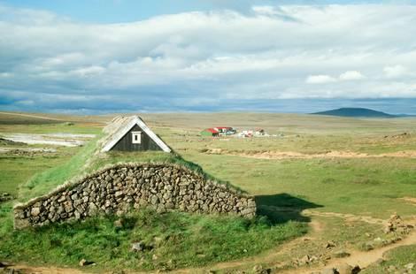 Ein Steinhaus mit Grasdach in einer Fjordlandschaft