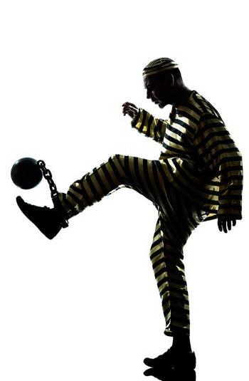Ein in Ketten gelegter Gefangener kickt seine Eisenkugel weg.