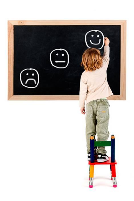 Kind auf Stuhl malt immer stärker lächelnde Smileys auf Tafel