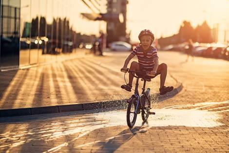 Kleiner Junge fährt kreischend auf Kinderfahrrad durch eine Pfütze und reißt die Beine hoch