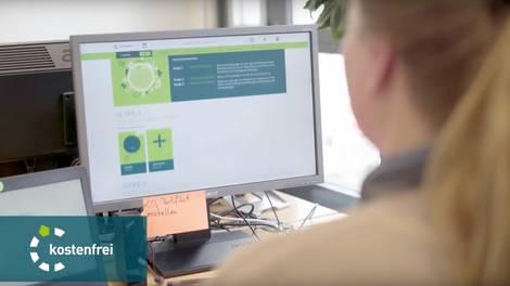 Mitarbeiterin vor Bildschirm mit CO2-Bilanzierungstool ecocockpit