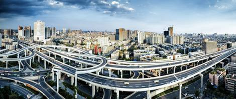 Ansicht einer mit Autostraßen überzogenen Stadt