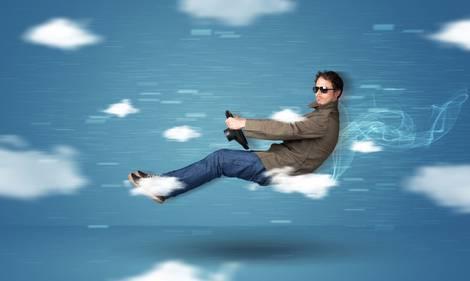 Ein Mann fährt Auto ohne Auto vor einem Wolkenbild.