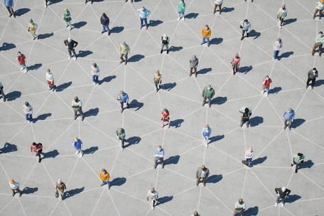 Menschen, von oben gesehen, auf einem Raster stehend, mit deutlichem Abstand
