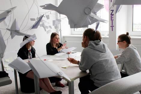 Menschen entwickeln in einer Gruppe um einen Tisch Ideen für Zukunftstechnologien