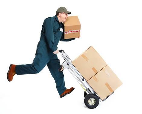 Ein fröhlicher Paketbote liefert Pakete auf einer Sackkarre und auf der Schulter