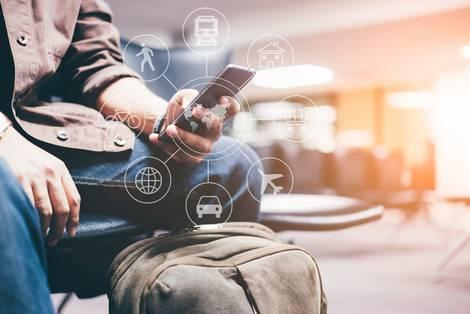 Mann mit Smartphone in der Hand wählt verschiedene Verkehrsmittel aus