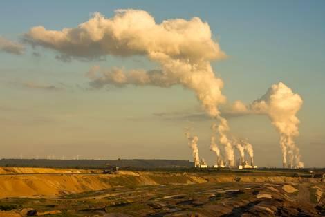 Kohlekraftwerk mit rauchenden Kühltürmen am Horizont