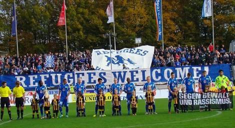 """Fan-Initiative Oldenburg mit Bannern """"Refugees welcome"""" im Stadion, davor Fußballmannschaft"""