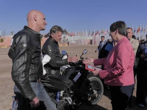 Umweltministerin Barbara Hendricks begrüßt zwei Elektromotorradfahrer nach ihrer Tour von Berlin nach Marrakesch