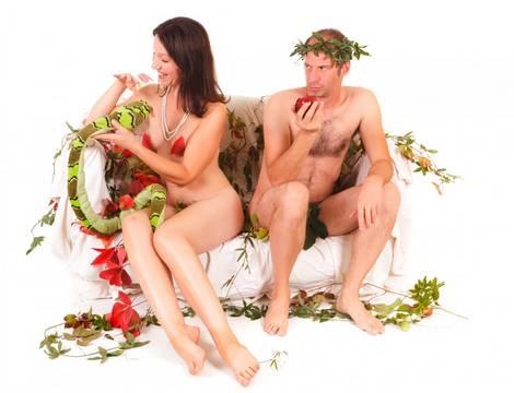 Ein Pärchen, das Adam und Eva darstellen soll, sitzt nackt auf einer Bank. Sie spielt mit einer Schlange, er mit einem Apfel.
