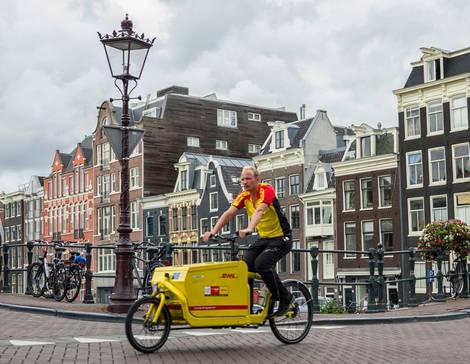 Lastenradfahrer auf Brücke in Amsterdam