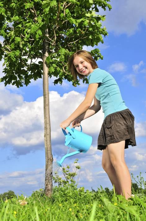 Junge Frau gießt mit Gießkanne Baum