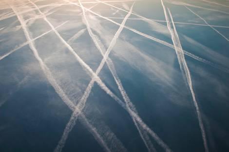 Kondensstreifen am Himmel, das Bild ist jedoch gespiegelt, die Kondensstreifen scheinen auf dem dunklen Himmelshintergrund zu liegen.