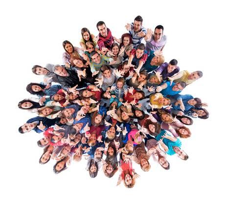 Eine Gruppe verschiedenster Menschen steht in einem vollen Kreis und reckt die Arme nach oben