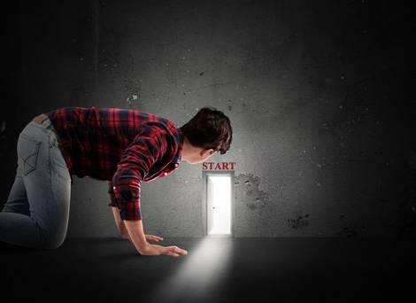 Mann schaut durch eine winzige Tür auf dem Boden knieend in einen anderen Raum, aus dem helles Licht durch die Türöffnung fällt.