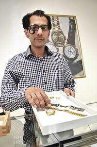 Pfandleiher Malik mit Tablet mit Schmuck