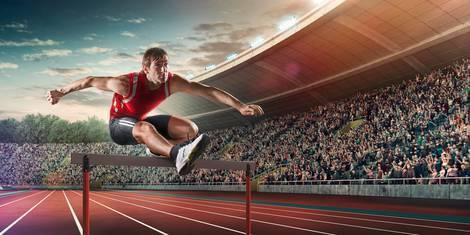 Leichtathlet überspringt Hürde im Stadion